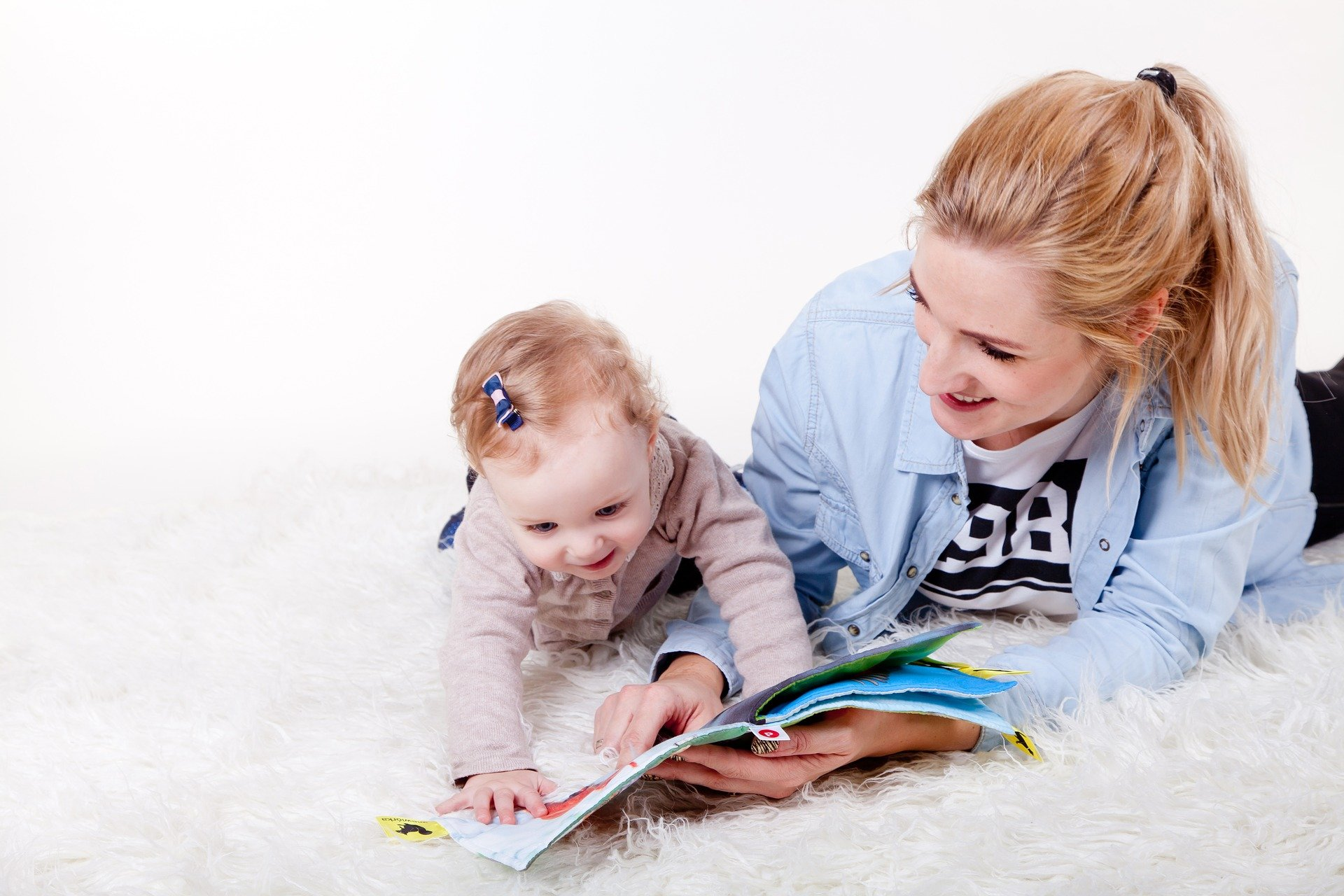 mum and baby tummy time. Baby has a book and mum is reading it